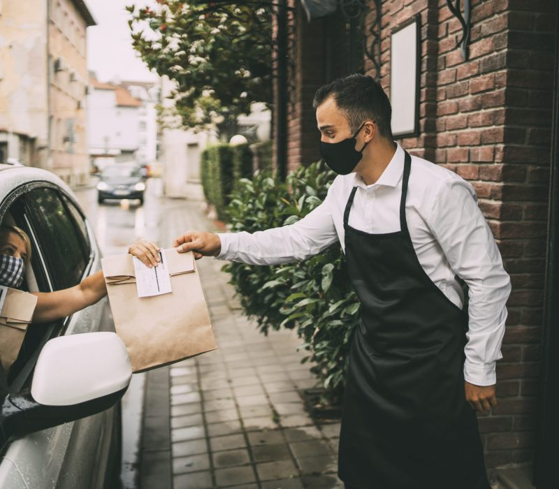Waiter wearing protective face mask is giving disposable package with food  to pretty female driver outside a restaurant.